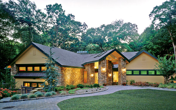 stylish green house plan with stone walkway and driveway