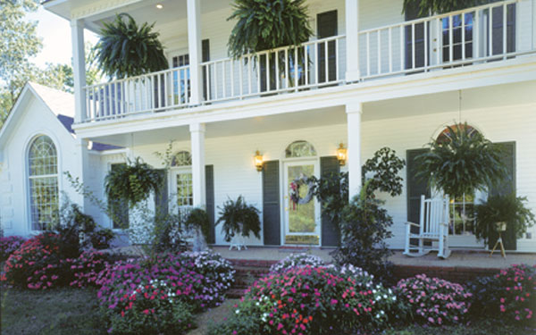 southern plantation style house with amazing flower garden