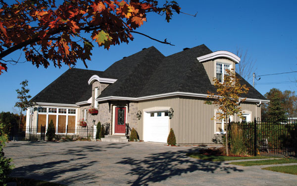 Country French house deisn with permeable paver driveway