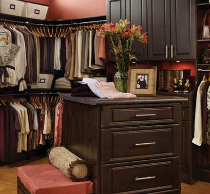 dark wood cabinetry in this luxury master bedroom walk-in closet
