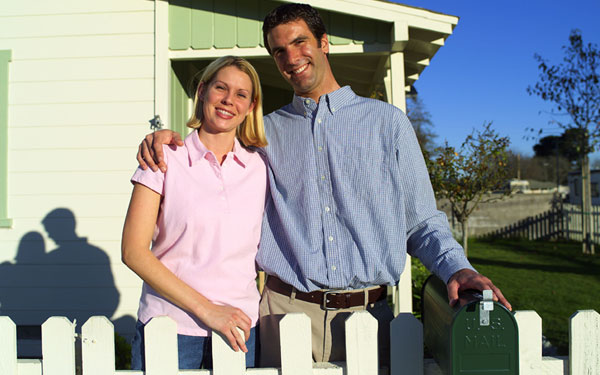 happy couple by a fenced home