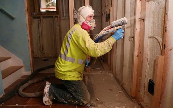 man spraying foan insulation in home