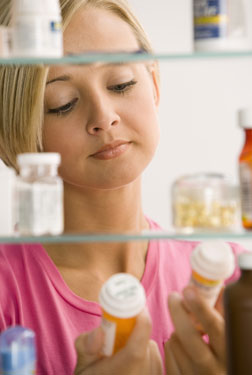 woman checking medicine cabinet
