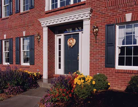 beautiful colonial home entry with fall landscaping