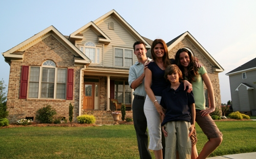 family in front of their dream home