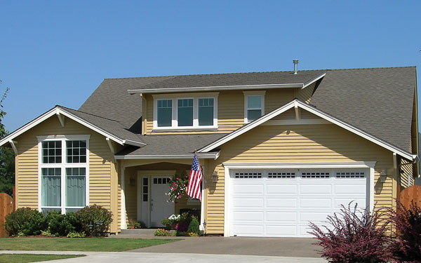 Bungalow style home with American flag hung in front