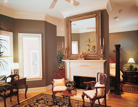Large square mirror above fireplace in master bedroom
