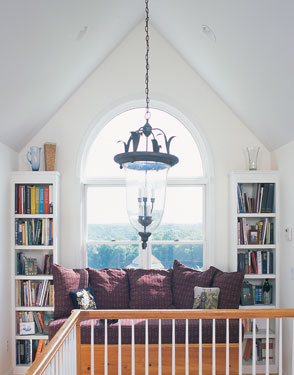 narrow bookcases flanking a large arched window