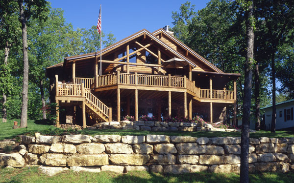 log home with rock landscaping wall