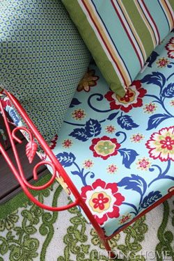 bold patterened chair cushion on red wrought iron chair