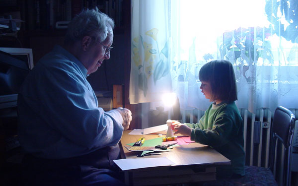 grandpa making crafts with young granddaughter