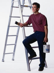 man leaning on ladder with paint can