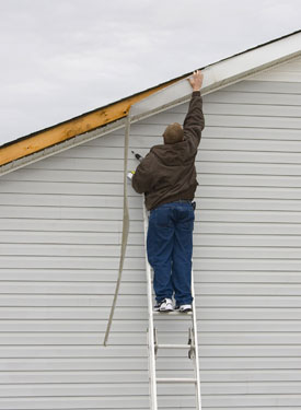 man fixing roof on ladder
