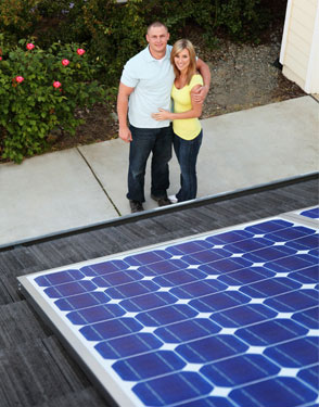 couple by home with solar panels on roof